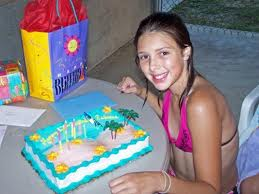 Young girl smiling in front of her beach themed birthday cake