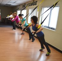 Women suspended from the wall by rope in fitness class