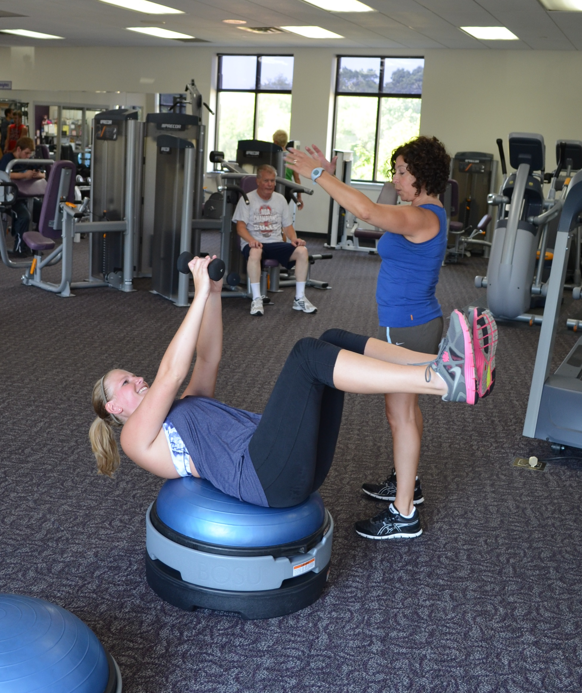 Woman exercising on a strengthening ball with an instructor