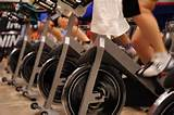A row of indoor bicycles with people taking a spin class